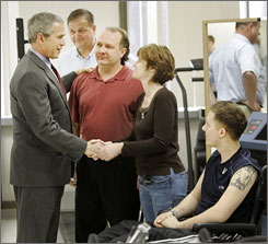 President Bush, left, visited Walter Reed Army Center on March 30.  Left to right are physical therapist Bob Bahr, Mark Ecker and Debra Ecker of East Longmeadow, Mass., parents of Sgt. Mark Ecker II, right, who was wounded by an IED in Iraq.