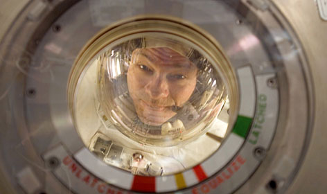 Commander Michael Lopez-Alegria peers through a window on the InternationalSpace Station in February. Crewmembers can spend months at a time in the orbiting lab.