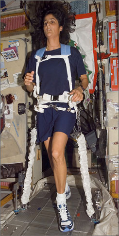 Astronaut Sunita L. Williams, equipped with a bungee harness, exercises on the Treadmill Vibration Isolation System (TVIS) in the Zvezda Service Module of the space station. Williams is participating, remotely, in the Boston Marathon.