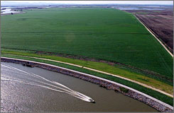 A boat passes Webb Tract farmland as it makes its way through the Sacramento-San Joaquin Delta near Isleton, Calif. Forecasts of sea level rise under global warming threaten the fresh water of the delta, which provides water to 23 million Californians.