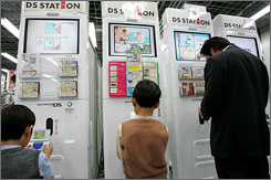 A man and youngsters play Nintendo's demo video games in Tokyo. In Japan, a key market, Wii has outsold the PlayStation 3 almost three-to-one since the machines went on sale late last year.