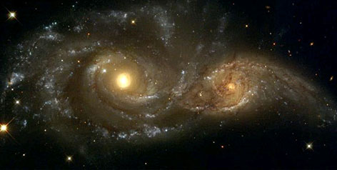 A near galactic-collision between NGC 2207 (left) and IC 2163 captured by the Hubble Space Telescope. Scientists predict the Milky Way will merge with its neighbor Andromeda in about 5 billion years.