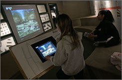 Amber Whitcomb takes the interactive video tour of Fort Ancient as her mother, Cindy Whitcomb, watches at right, at the Museum Center in Cincinnati. Fort Ancient is a 2,000 year old earthworks site about 30 miles north of Cincinnati that features 18,000 feet of earthen walls.