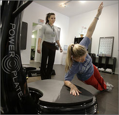 Trainer Michela Rossi watches Amy Allen as she exercises on a Power Plate fitness machine in Chicago. Researchers say the science is thin and too little is known about the long-term effects of the vibration machines.