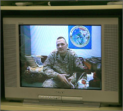 Sgt. Chad Matthews watched his son being born via a Freedom Calls video conference. Matthews is shown in Iraq on the main screen of a television monitor while his newborn son, Braxton, held by his wife Cynthia, is shown in the smaller picture inset at lower right.