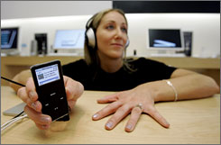 Nessia Frazier listens on an iPod nano at the Apple store in Palo Alto, Calif.. The recent rollout of songs without copy protection software on iTunes has raised questions about the  inclusion of personal data in purchased music tracks.