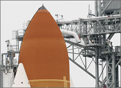 Employees work near the top of the external tank attached to space shuttle Atlantis. The shuttle is scheduled to lift off for a  mission to the International Space Station, Friday night.