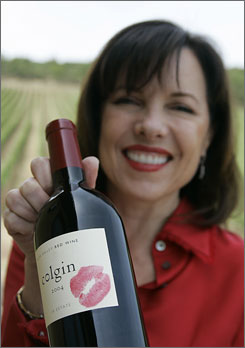 Ann Colgin holds up a feshly-kissed bottle of Cabernet Sauvingon. For years, she has added a playful seal of authenticity to bottles of her wines, a bright-red lipsticked kiss on the label. But with concerns growing about counterfeiting, she and other Napa Valley winemakers are turning to higher-tech methods of assuring buyers they are taking home genuine wine.