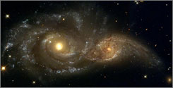 """The """"kick"""" from an enormous burst of gravitational radiation that occurs during a collision of black holes could knock a black hole clear out of its galaxy. Here, a near-collision between two spiral galaxies in the direction of the constellation Canis Major."""