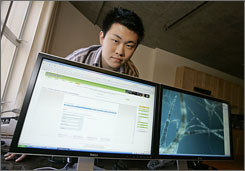Jared Kim, 19, stands behind a computer screen displaying the web page to his company called Stalkerati.com at his loft in San Francisco.