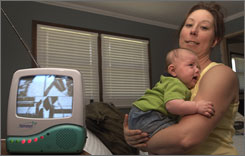 Natalie Meilinger holds her son Jack, 3 months, in their Palatine, Ill., home near a baby monitor that's receiving a transmission from the space shuttle this week. 
