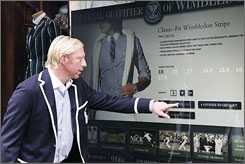 Former Wimbledon Champion Boris Becker demonstrates the interactive 24 hour 'window shopping' touch screen at the Polo Ralph Lauren store in London.