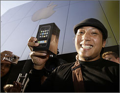 John Mariano, 27, is surrounded by onlookers and media as he leaves the Apple Store with his iPhone Friday, June 29, 2007, at The Grove shopping center in Los Angeles.