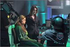 Vanessa Arteaga, left, of the San Francisco Optx, plays a shutout Dead or Alive match as her General Manager Kat Hunter, right, looks on at the Championship Gaming Series in Los Angeles.  DIRECTV is showing CGS games.