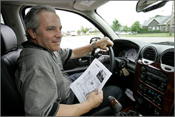 Mark Evangelista uses a directions printed out from a computer while driving in Novi, Mich. Evangelista, who leased a GMC Envoy for his business, passed on the in-dash navigation system because of the $25 it would add to his monthly payment.