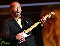 Peter Moore demonstrates the new XBOX game 'Rock Band' during Microsoft's E3 media briefing in Santa Monica on July 10.