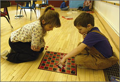 "Sarah Abbott, 8, and Loren Wilson, 7, right, playing checkers at Nye Elementary School in Montana. A computer program that plays checkers has ""solved"" the popular game."