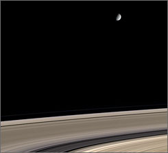 Small moon, big questions: Enceladus, photographed with Saturn's rings, is only 318 miles wide but was captured blasting watery material 270 miles into space.