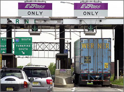 Cars and a truck go through the E-ZPass on the New Jersey Turnpike. Besides allowing drivers to go through toll plazas without forking over cash, E-Z Pass and other electronic toll collection systems leave a record of where the drivers have been, and when.