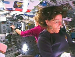 Endeavour mission specialist Barbara Morgan holds a floating necklace in her mouth as she works on the flight deck of the orbiter with fellow robot arm operator Tracy Caldwell, left, as the crew prepares for inspection of the shuttle's thermal protection system.