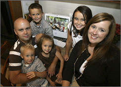 Mark and Corrie Pankow with their children, clockwise from upper left, Carter (6), Makenzie (9), Davis (3) and Sydney (5)  in their home in Peoria, Ariz. 