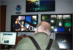 Undersea explorer Bob Ballard, on monitor at left, explaining a new communications system to AP science writer Randy Schmid, right, at NOAA headquarters. Ballard is testing the new communications system for NOAA.