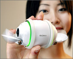 A model displays Sony's robotic music player Rolly, equipped with 1GB built-in flash memory and mounted stereo speakers on an egg-shaped body.