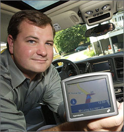 Austin Sweazy poses with his new GPS navigation device in his vehicle at his home in Salem, Mass. A thief had previously smashed his windshield and stole his first navigation unit.