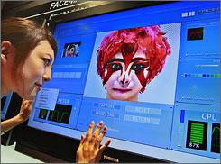"Toshiba's Facemation, seen here, features the ""SpursEngine"" processor. The SpursEngine's can do real-time, 3D ""face morphing"" of hairstyles and makeup on actual video of individuals."