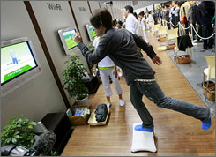 A model demonstrates Nintendo's Wii Fit, which allows players to weigh themselves and play fitness games, during a press event in Makuhari, east of Tokyo. Nintendo's group sales more than doubled  in the six months leading to Sept. 30.