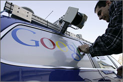 Decal worker Todd Martin puts on a Google sticker on a VW Passat called Junior, the Stanford University team's self-driving car entered into the DARPA Urban Challenge, at a decal shop in Redwood City, Calif.
