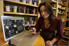 Actress and photographer Bree Michael Warner poses with her Helio mobile phone as she uploads data in real time to her MySpace web account from a coffee shop in the Toluca Lake area of Los Angeles.