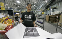 "Louisa Quintero giftwraps an Internet book order at the Barnes & Noble Distribution Center in Monroe Township, N.J. in this 2006 file photo. The Monday after Thanksgiving, or ""Cyber Monday,"" marks the first big online shopping surge for many merchants."