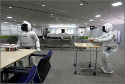 Honda's humanoid robots named Asimo work together to serve coffee during a demonstration at Honda's labs in Tokyo. Honda says its robots are now ready to work in pairs - and they can even serve drinks.