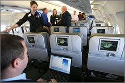 "Brad Garlinghouse, left, senior vice president of Yahoo, demonstrated the capabilities of a laptop during a media preview flight aboard ""BetaBlue,"" JetBlue's Airbus A320 aircraft equipped with an onboard wireless network."