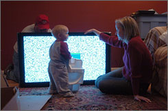 Beth Bruederle watches 13-month-old son Liam while her husband, J.B., sets up their 46-inch high-definition TV in Chicago earlier this month.