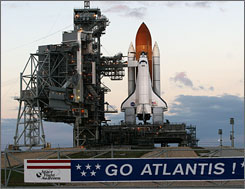 Atlantis sits on the launch pad on December 9 after NASA postponed its launch until early 2008.    Continuing issues with the shuttle's fuel tank will push Atlantis' expected launch date a few days or weeks.