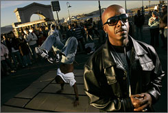 MC Hammer, Chief Strategy Officer for DanceJam.com, poses for a photograph as a dancer performs near Pier 41 in San Francisco. The site will try to upstage YouTube as a hub for watching dance videos.