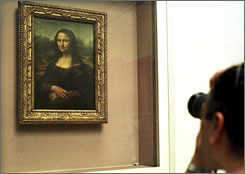 A man takes a photograph of Leonardo da Vinci's Mona Lisa in the Louvre in Paris. A researcher has uncovered evidence that apparently confirms the identity of the woman behind the Mona Lisa's iconic smile.