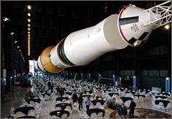 Workers prepare for the dedication of a newly renovated Saturn V moon rocket in Huntsville, Ala. The work was the cornerstone of a $23.4 million project at the U.S. Space & Rocket Center, where the rocket spent 35 years outdoors.