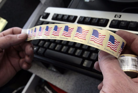 Robert McEvilly, owner of Postal Pack n Ship, holds a roll of a USA First-Class stamps in Glendale, Calif.  Because many people around the world pay bills and send mail digitally, the U.S. Postal Service and its counterparts in other countries are expanding into electronic services and tapping technology to cut costs. 