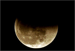The moon starts a total lunar eclipse in Jakarta, Indonesia. The moon will turn an eerie shade of red for people in the western hemisphere late Wednesday and early Thursday.