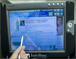 Kyle Piechucki, CEO and President of InfoSlate, demonstrates the InfoSlate device in New York. The touch-screen tablet are marketed to doctors for use in their offices by patients waiting for appointments.
