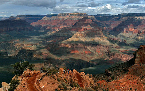 With the North Rim in the background, tourists hike along the South Rim of the Grand Canyon. Scientists have found that the western half of the canyon began to open up 17 million years ago and joined with the eastern side, which formed starting 6 million years ago.