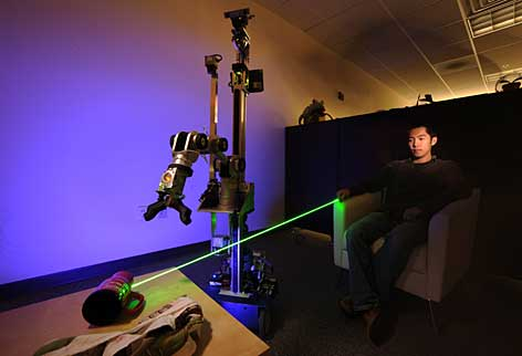 Using a laser pointer, Hai Nguyen, a research student in Georgia Tech's Ph.D. program in robotics, instructs the EL-E laser-directed robot to pick up a cup.  The robot will be tested this summer in a real-world setting involving patients with a degenerative disease.