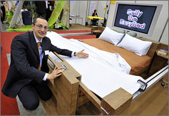 Enrico Berruti poses with his invention, a self-making bed during the 36th International Exhibition of Invention in Geneva. More than 700 exhibitors from 45 countries attend the world's largest exhibition devoted to innovation.