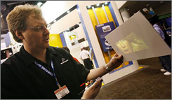 Microvision's Russell Hannigan demonstrates a handheld projector hooked up to an iPod during the CTIA Wireless Show in Las Vegas. Companies are racing to develop gadgets that project what's playing on the small screen onto walls, table cloths and other handy surfaces.
