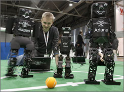 Konrad Meier adjusts his humanoid robot 'Juergen' at the RoboCup German Open. The world's leading fair for industrial technology, with about 5,100 exhibitors from 62 nations, opened to the public on Monday.
