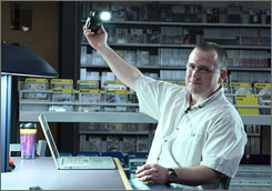 David Hobby, who runs a photography website, holds one of the small flash units he uses for creative photographic lighting.
