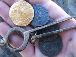 A close-up of a Spanish gold coin, three Portuguese silver coins and a pair of brass dividers that were found from a shipwreck off the coast of Namibia.  All the coins were minted in the late 1400s or early 1500s.